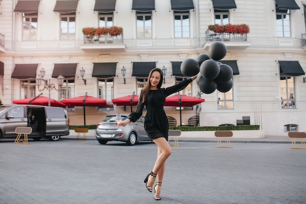 Portrait en pied d'une superbe femme brune en chaussures élégantes dansant avec des ballons de fête dans la rue