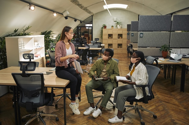 Portrait en pied de trois hommes d'affaires contemporains portant des masques tout en discutant d'un projet de travail dans un bureau moderne post pandémie