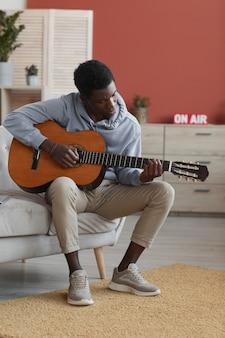 Portrait en pied vertical de jeune homme afro-américain jouant de la guitare acoustique alors qu'il était assis sur le canapé à la maison