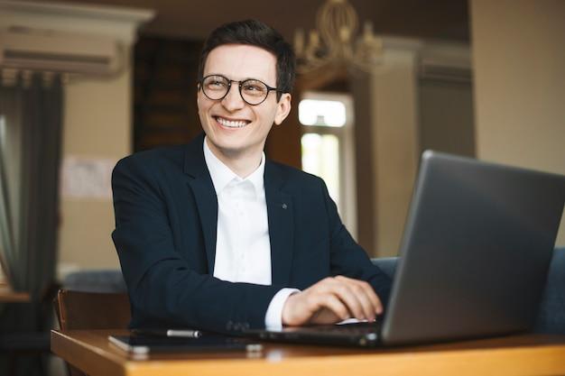 Portrait d'un pigiste adulte attrayant portant costume et lunettes à la voiture en souriant tout en travaillant sur son ordinateur portable assis dans un café.