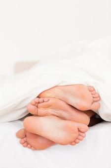 Portrait d'une pile de pieds dans un lit