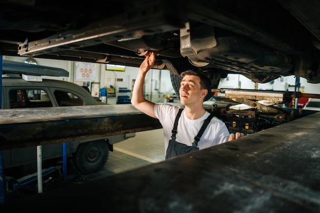 Portrait de plan moyen d'un beau mécanicien automobile professionnel concentré en uniforme, debout dans l'inspe...
