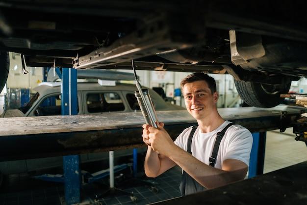 Portrait de plan moyen d'un beau mécanicien automobile professionnel masculin souriant en uniforme, debout dans l'inspe...