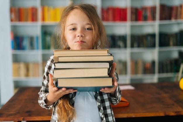 Portrait de plan moyen d'une jolie écolière élémentaire tenant une pile de livres dans la bibliothèque à
