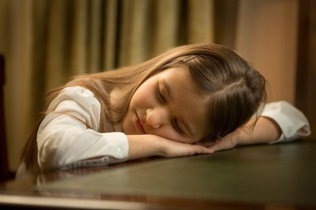 Portrait de plan rapproché d'écolière fatiguée mignonne dormant sur le bureau