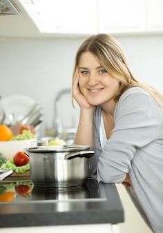 Portrait de plan rapproché de femme heureuse faisant cuire sur la cuisine moderne