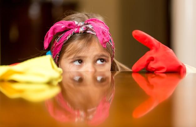 Portrait de plan rapproché de fille regardant le doigt dans des gants couverts de poussière