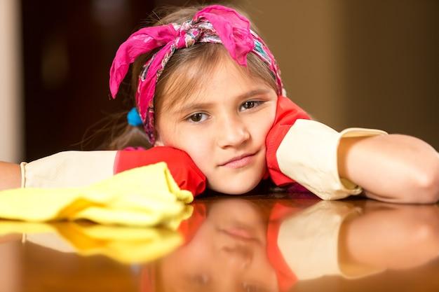 Portrait de plan rapproché de petite fille triste dans les gants en caoutchouc nettoyant la table en bois