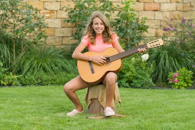 Portrait en plein air d'une adolescente avec guitare