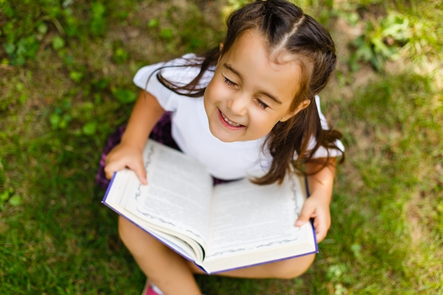 Portrait en plein air d'une adorable petite fille lisant un livre dans le jardin