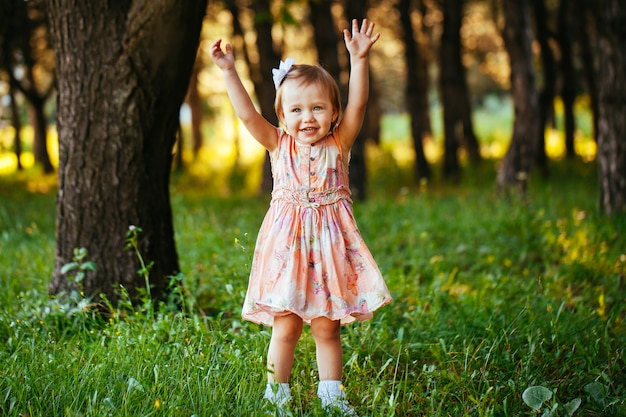 Portrait en plein air d'une adorable petite fille souriante en jour d'été
