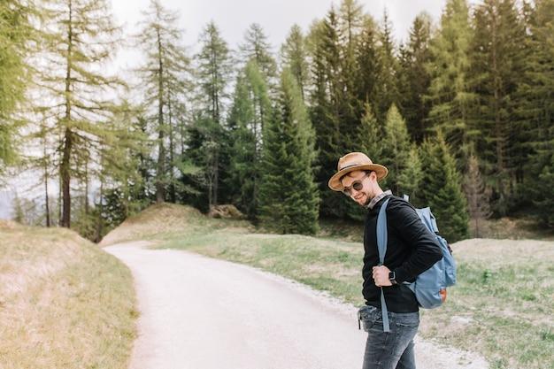Portrait en plein air de beau mec élégant pensivement debout sur la route, au repos après une longue randonnée