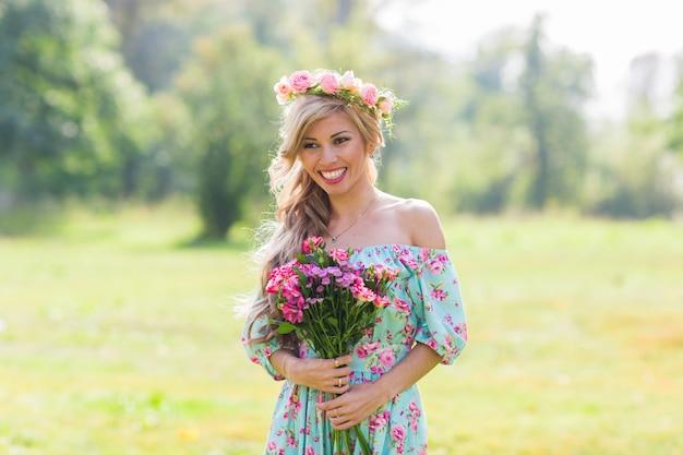 Portrait en plein air d'une belle femme blonde. jolie fille heureuse dans un champ avec bouquet de fleurs.