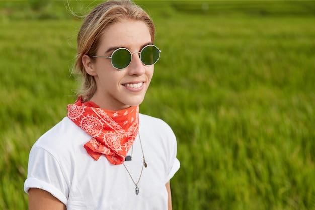 Portrait en plein air de la belle femme souriante habillée en t-shirt décontracté et porte des lunettes de soleil, se dresse contre l'herbe verte, se promène