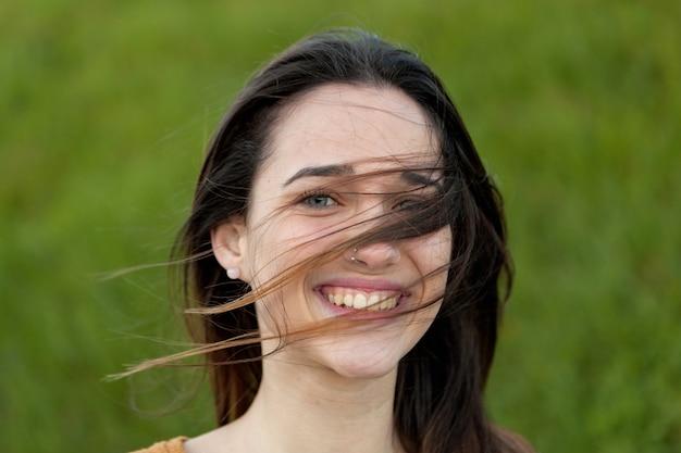 Portrait en plein air d'une belle fille qui rit tandis que le vent bouge ses cheveux