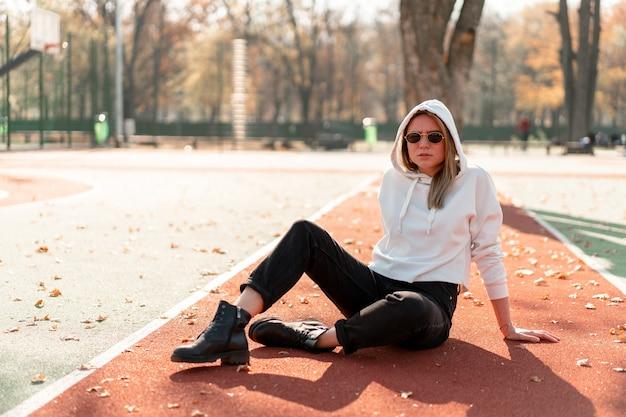 Portrait en plein air d'une belle jeune femme avec de longues lunettes de soleil et un pull à capuche blanc assis sur la piste du terrain de sport. passe-temps d'été de la culture des jeunes