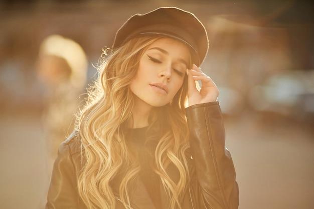 Portrait en plein air de la belle jeune femme à la mode et sensuelle en veste de cuir noir et chapeau élégant avec maquillage et yeux fermés posant dans la rue au coucher du soleil