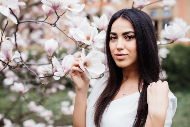 Portrait en plein air d'une belle jeune femme près de magnolia avec des fleurs.