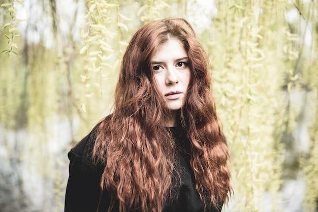 Portrait en plein air de belle jeune femme rousse