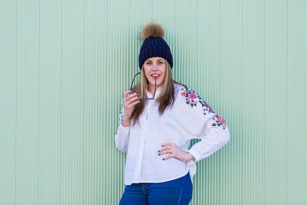 Portrait en plein air d'une belle jeune femme souriante et s'amuser par-dessus le mur vert