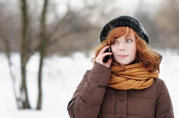 Portrait en plein air de belle jeune femme avec téléphone portable en hiver