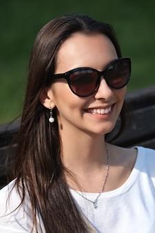 Portrait en plein air de belle jeune fille souriante en grosses lunettes de soleil