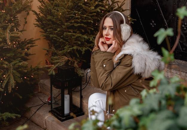 Portrait en plein air de la belle jeune fille souriante heureuse porte un manteau de fourrure près de sapin de noël décoré
