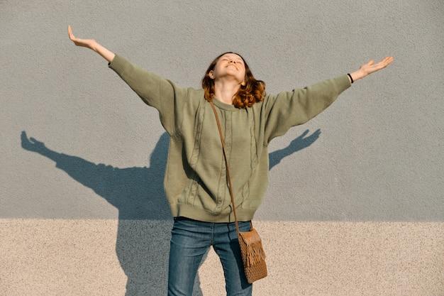 Portrait en plein air de bonne adolescente avec les mains vers le haut