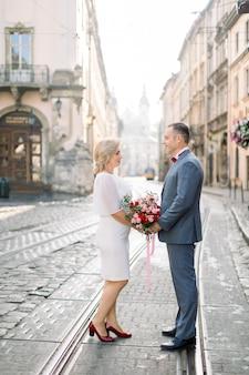 Portrait en plein air d'un couple romantique dans la vieille ville. bel homme mûr en costume bleu profitant de la promenade avec sa superbe femme jolie blonde en robe, debout se regardant