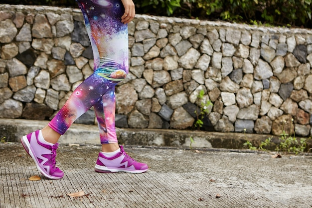 Portrait en plein air de coureuse avec des jambes athlétiques en forme portant des baskets violettes marchant le long d'un chemin en béton dans un parc urbain, reprenant son souffle après un entraînement intensif, se préparant pour le marathon
