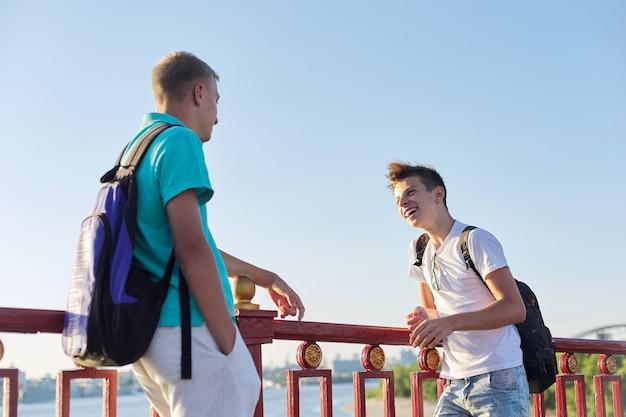 Portrait en plein air de deux amis adolescents garçons de 15, 16 ans, riant, parlant en journée ensoleillée, debout sur un pont au-dessus de la rivière. mode de vie urbain, ados, amitié, communication