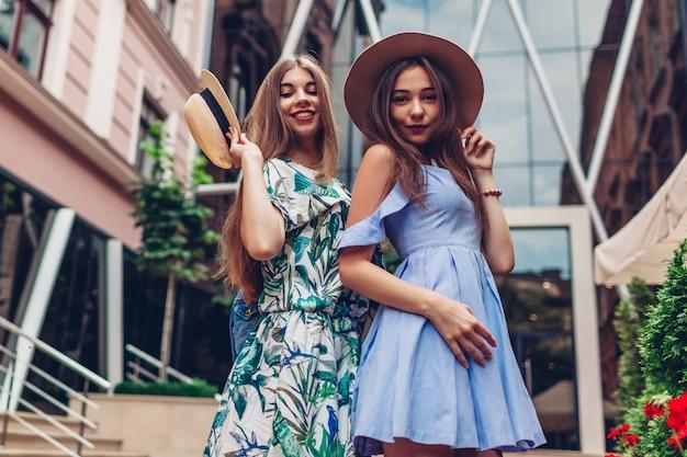 Portrait en plein air de deux jeunes femmes magnifiques. filles portant des vêtements et des accessoires élégants en ville. meilleurs amis