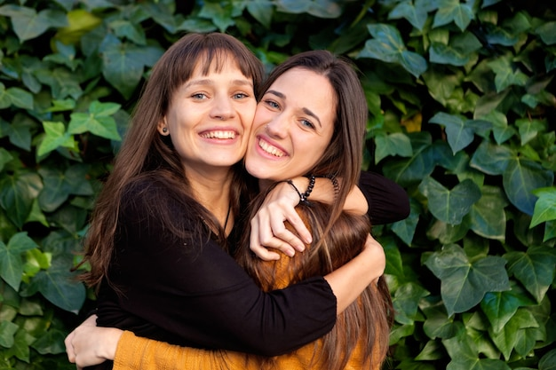 Portrait en plein air de deux soeurs heureuses dans un parc