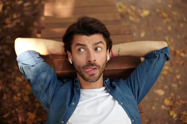 Portrait en plein air drôle de joli jeune homme barbu allongé sur un banc, gardant les mains sous sa tête et regardant ailleurs, levant les sourcils et montrant la langue