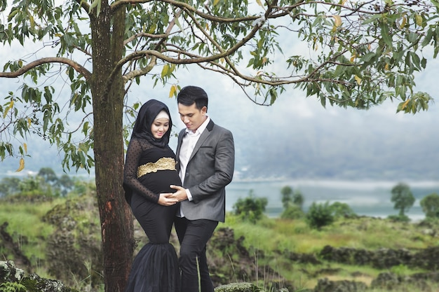 Portrait en plein air du moment romantique du couple enceinte sous l'arbre