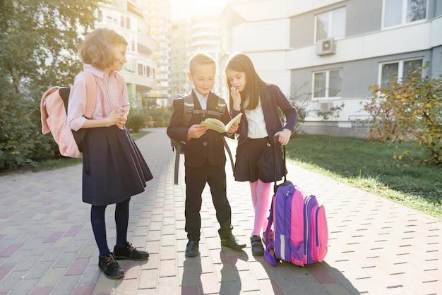 Portrait en plein air d'écoliers souriants à l'école primaire