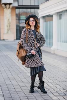 Portrait en plein air d'élégante jeune femme avec sac à dos marron portant manteau et chapeau. jolie femme aux cheveux bouclés parlant au téléphone tout en buvant du café dans la rue et en attendant des amis.