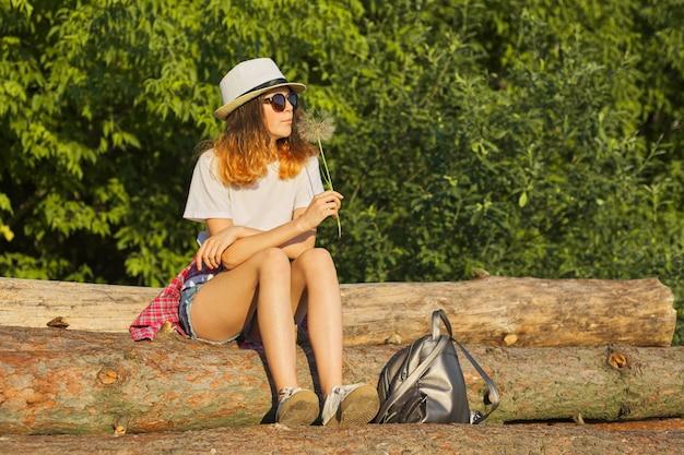 Portrait en plein air d'été d'adolescente romantique au chapeau avec gros pissenlit moelleux