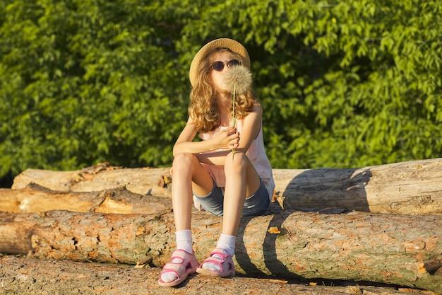 Portrait en plein air d'été de fille romantique avec gros pissenlit moelleux
