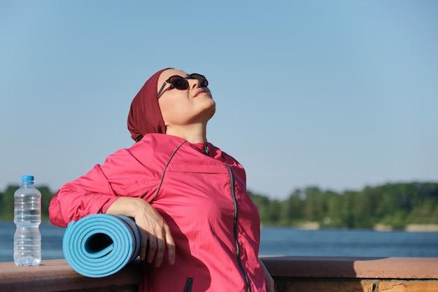 Portrait en plein air d'une femme d'âge en tenue de sport avec tapis de yoga
