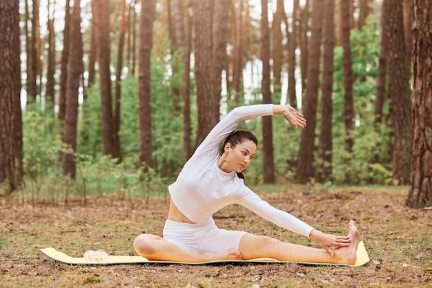Portrait en plein air d'une femme aux cheveux noirs avec un corps parfait en vêtements de sport blancs