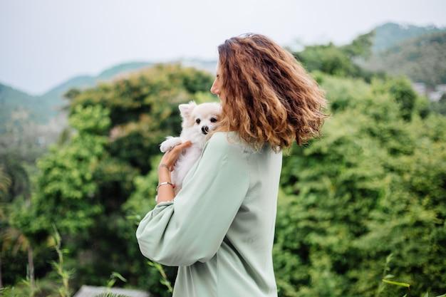 Portrait en plein air de femme bronzée européenne bouclés détient happy pet dog pomeranian spitz