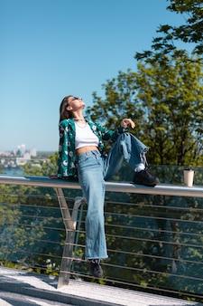 Portrait en plein air de femme en chemise verte décontractée et jeans à la journée ensoleillée sur le pont avec vue imprenable sur la ville le matin