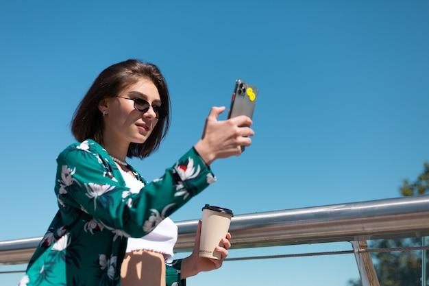Portrait en plein air de femme en chemise verte décontractée et jeans à journée ensoleillée se promène sur le pont avec une tasse de café à la recherche sur l'écran du téléphone