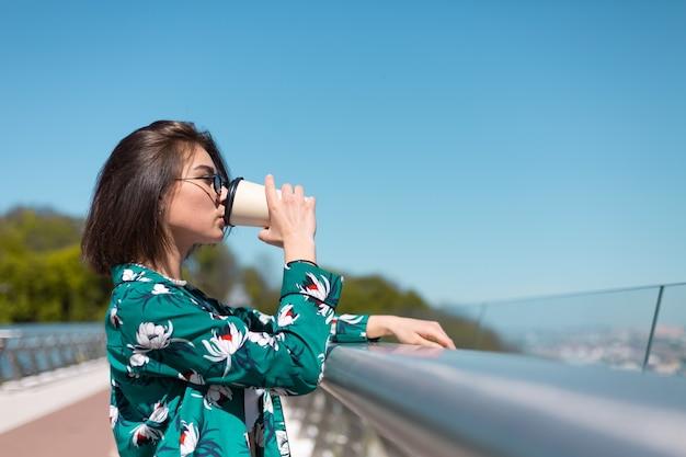 Portrait en plein air de femme en chemise verte avec tasse de café en profitant du soleil, se dresse sur le pont avec vue imprenable sur la ville le matin