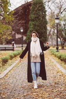 Portrait en plein air de femme dans le parc portant manteau noir d'hiver et écharpe blanche