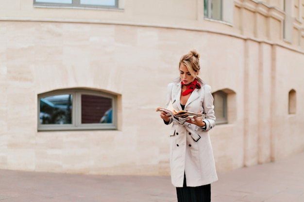 Portrait en plein air d'une femme européenne déçue en long manteau debout dans la rue et regardant vers le bas