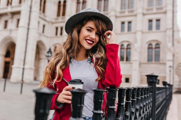 Portrait en plein air d'une femme glamour avec une coiffure ondulée, boire du café