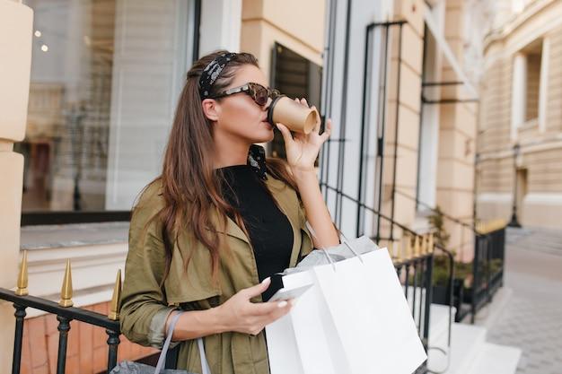 Portrait en plein air de femme gracieuse obsédée par le shopping