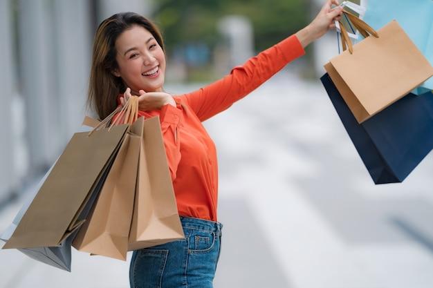 Portrait en plein air de femme heureuse tenant des sacs à provisions et visage souriant au centre commercial